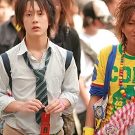 A ganguro boy walking next to his good-looking friend.