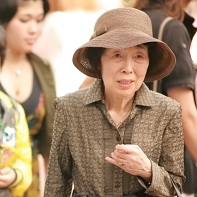 An older Japanese lady dressed in brown.