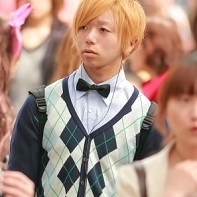 Japanese boy with blond hair, black bow-tie and checkered sleeveless sweater. What a crazy combination!