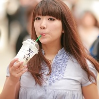 Japanese girl drinking absent-mindedly from a Starbucks cup with a straw. Usually eating and drinking in public is frowned upon, but apparently she doesn't care.