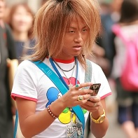A ganguro boy with a tan, lightened hair and colorful accessories.