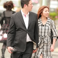 A Japanese couple dressed in black & white walking hand-in hand. Note the Gothic Lolita in the background.