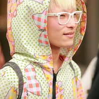 Japanese guy with a colorful hoodie and white glasses.