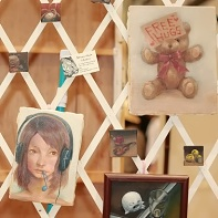 "Various small paintings by Natsumi Okuda, one with a teddy bear holding a ""Free Hugs"" sign."