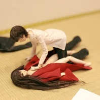 A couple of small dolls artfully arranged in a loving position.