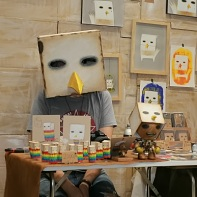 A Korean illustrator dressed up as the main character of his artworks - some kind of boxy bird.