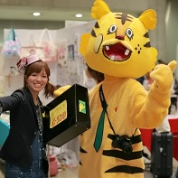 Two people - one with a tiger suit - promote their booth by walking around.
