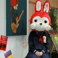 "I think this person in a schoolgirl's uniform with an oversized red bunny head is not only presenting the pictured paintings, but also a band called ""Amanda""."