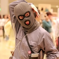 This Japanese guy dressed in a gray jumpsuit and a balaclava was walking around beating a drum and promoting some booth number.