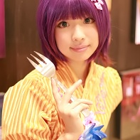 A female cosplayer with a purple wig in her booth selling photos of herself modeling.
