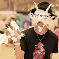 A paper artist wearing two of his creations - a demon mask and a dragon hand puppet.