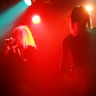 """Neu!-r-v-verderber"" and Tak of Neurotic Doll performing in red backlight."