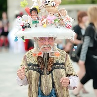 Eijirō Miyamae wearing his female cosplay and a big hat covered with dolls and other small figurines.