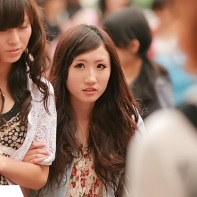 A Japanese girl with long wavy hair giving a fearful look back at me.