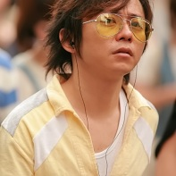 Japanese guy with yellow sunglasses and matching t-shirt.
