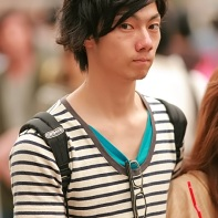 A passer-by wearing a striped t-shirt throws a wary glance.