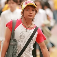 A trendy boy with the signature ganguro tan and colorful fashion.