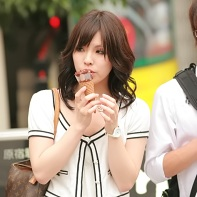 Japanese girl dressed in white eating an ice-cream cone.