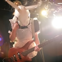 Bassist Hayashibe of Ray Trak wearing a maid costume and a white rabbit mask.