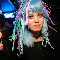 DJ Mikan with blue wig and plastic hair extensions.