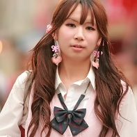 Japanese girl with long, wavy brown hair, fake eyelashes and white shirt with pink vest.