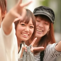Three Japanese girls smiling towards the camera.