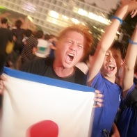Japanese soccer fans celebrating with the white-and-red hinomaru flag.