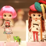A Blythe doll in a colorful Tokidoki dress walking Bastardino the cactus dog (left) and a Blythe doll by Naito Yamada (やまだないと) displaying a manga artist wearing many stereotypical berets.