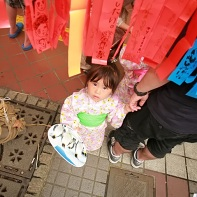 Young girl in yukata under red streamers.
