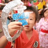 Young boy holding a part of a mobile-like decoration.