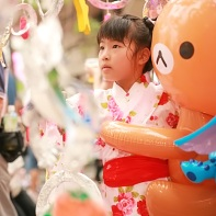 Young girl wearing a yukata and a blow-up anime bear.