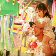 A young girl on her father's shoulders checking out colorful decorations made from plastic bottles.