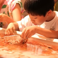 A popular pasttime on festivals: Boy fishing for goldfishes.