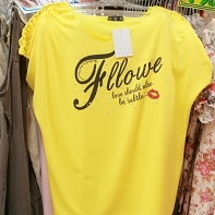 "A yellow t-shirt with the almost incomprehensible print ""This heart is very very ner you - Fllowe - love should also be subtle""."