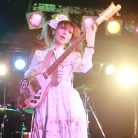 The female bass player Ura (裏) of 遺伝子組換こども会 performing next to the singer Nobita.