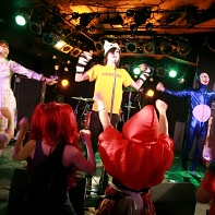 The Japanese punk rock band 遺伝子組換こども会 (The Club of Genetically-engineered Children) giving dance instructions to the audience.