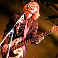 The orange-haired bass player Yogore (ヨゴレ) of 桃尻東京テレビジョン performing.
