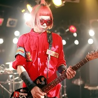 Sandoitchi de Hyakunijūpun?'s guitarist Hamu Takemura (竹村ハム) dressed in a red jumpsuit.
