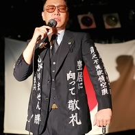 Minoru Torihada (鳥肌実) dressed in a serious suit covered with outrageous patriotic slogans.
