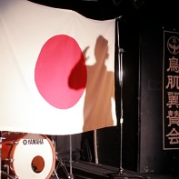 Behind him was an oversized Japanese national flag and a banner reading Torihada support meeting (鳥肌翼賛会).
