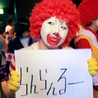 Two patrons of the Gantai Alice 3 event wearing Ronald McDonald cosplays and holding various signs.