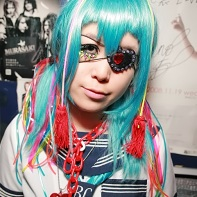 Japanese girl dressed in a sailor suit and wearing a blue wig with colorful decora accessories.