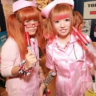 Two Japanese girls dressed as some scary nurses with huge syringes.