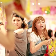 Two shopgirls shouting and making noise to attract costumers.