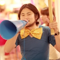 A Japanese guy with an oversized and sequined bow-tie using a megaphone to advertise bargains.