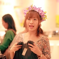 Girl sporting a flower chain headdress selling clothes.