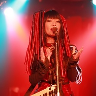 Singer Nekoi of Psydoll bathed in red light.