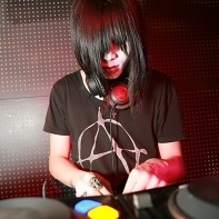 Japanese goth DJ Tetra wearing an anarchy t-shirt while deejaying.