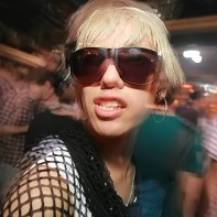 Guy with dark glasses and blonde hair on the dancefloor.