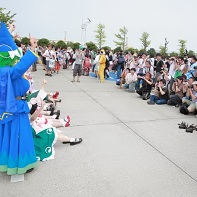 A large group of Touhou Project (東方Project) cosplayers (including Youmu Konpaku, Yuyuko Saigyouji and Mima) being photographed by an even larger crowd of photographers.